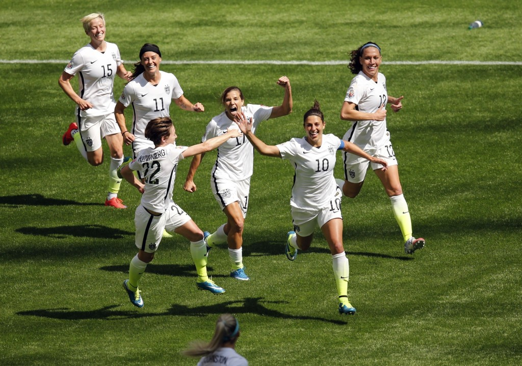 Carli Lloyd (10) and her teammates celebrate Lloyd's hat trick goal.